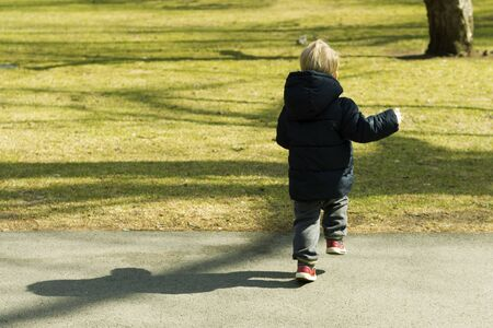 Runaway toddler in sunny park. Kid trying to catch wild squirell Stockfoto