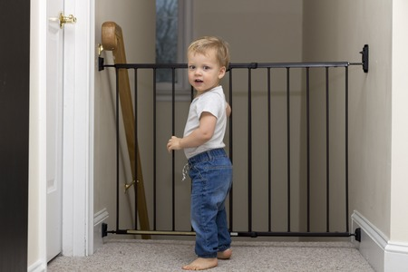 Cute Toddler Approaching Safety Gate Of Stairs At Home Stock Photo    98434205