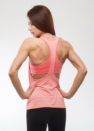 Happy young woman in sports clothing. Muscular fitness model on white background. Back view Stock Photo