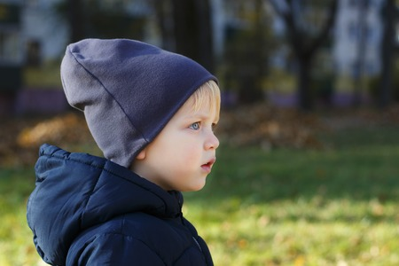 Dreaming boy in hat outdoor. Autumn shoot. Cute toddler profile portrait. Copy space