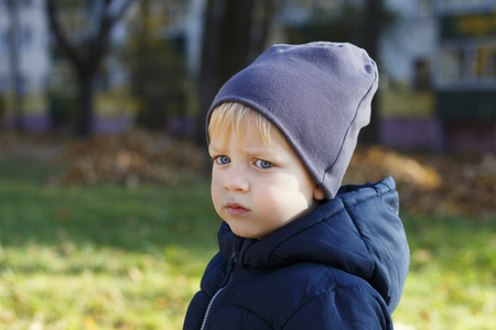 Sad boy in hat outdoor. Autumn shoot. Cute toddler profile portrait. Copy space