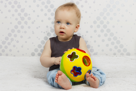 portrait of happy cute one year old baby boy siiting on the bed with a toy ball against abstract background Фото со стока