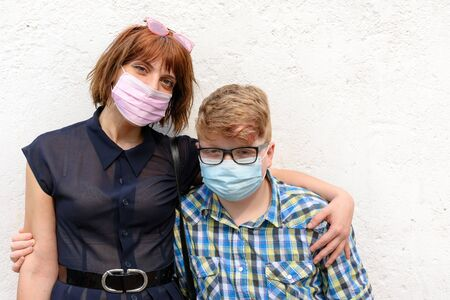 Sister wearing trendy glasses and little brother with glasses posing together looking at the camera.Young red-haired woman and boy wearing a surgical mask stand against a wall background. 版權商用圖片