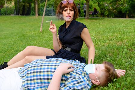 Young boy with surgical mask lying on the grass in the park near a sitting girl who smokes. Child dressed in a plaid shirt lying on the green field near a beautiful red-haired woman who smokes.