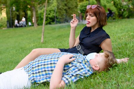 Young boy with surgical mask lying on the grass in the park near a sitting girl who smokes. 版權商用圖片
