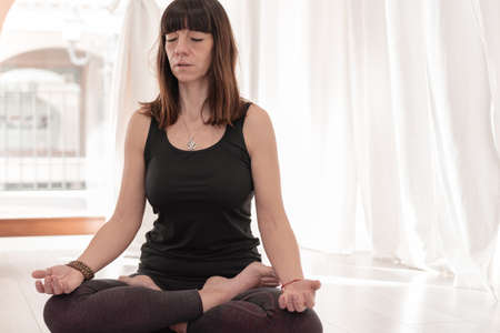 Yoga teacher sitting in the lotus position. Woman practicing Yoga. How to Keep Your Arms for a Kriya or Meditation.
