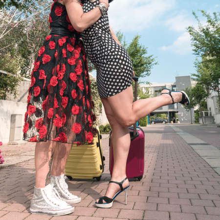 Cropped photo from below of two elegant tourist women walking with suitcases on the flowery street of the city. 免版税图像