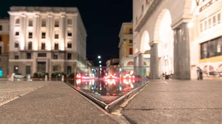Urban movement in a night square. Victory Square, Brescia, Italy.