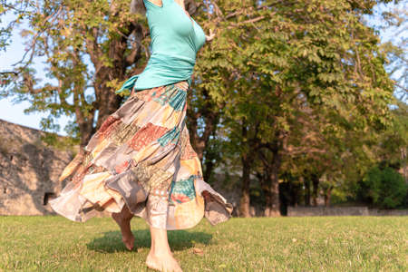 Beautiful barefoot girl in a long colorful skirt is dancing in natural background 免版税图像