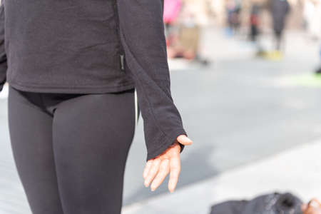 Yoga teachers protesting against the blockade and restrictions of Covid-19 in a square in Brescia, Italy. Detail of the hand of a woman who is standing in the mountain position.