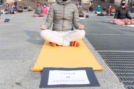 """Yoga teachers protesting against the blockade and restrictions of Covid-19 in a square in Brescia, Italy. Shot of the hands resting on the knees of the crossed legs. People are meditating. Written on the card: """"More yoga, less depression""""."""