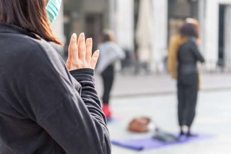 Yoga teachers protesting against the blockade and restrictions of Covid-19 in a square in Brescia, Italy. Female and male hands in a namaste or prayer gesture.