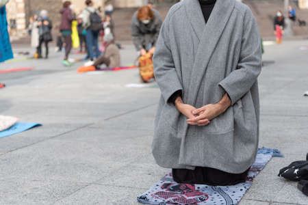 Yoga teachers protesting against the blockade and restrictions of Covid-19 in a square in Brescia, Italy. Man dressed fashion stands on his knees in prayer position.