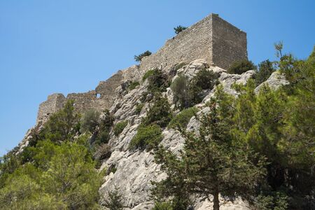 Remainders of stone walls of old medieval castle on the rock in Greece