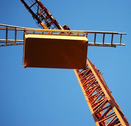 Square shot of orange crane on blue sky