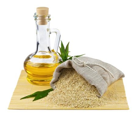 Vista macro di semi di sesamo in sacco di lino e bottiglia di vetro di olio di sesamo isolato su sfondo bianco Archivio Fotografico