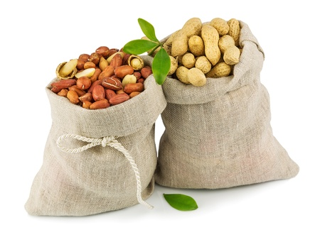Macro view of purified and raw peanut in flax sacks and green leaves isolated on white background Stock Photo
