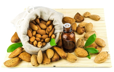 Almonds in the sack and almond oil on mat isolated on white background Reklamní fotografie - 18011104