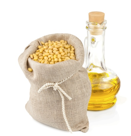 Macro view of pine nuts in flax sack and glass bottle of oil isolated on white background