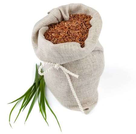 Macro view of sack of red rice with greens isolated on white background