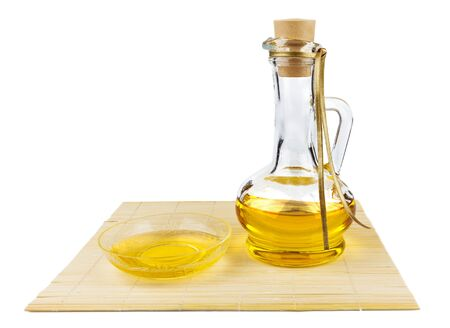 Glass bottle of oil and saucer with oil on the mat isolated on white background