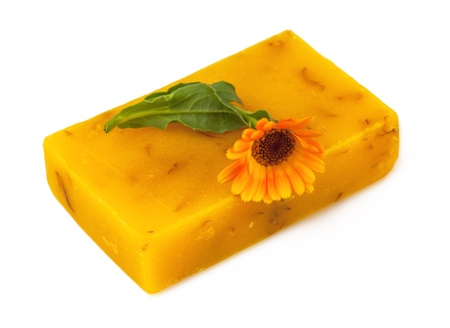 Macro view of handmade soap with marigold isolated on white background