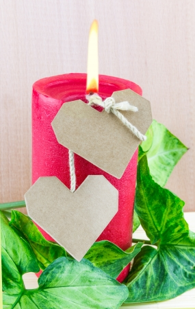 Two paper hearts and lighted red candle with green leaves Stock Photo - 18011111