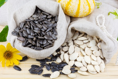 Macro view of raw sunflower and pumpkin seeds in flax sacks with flower and pumpkin on the mat Stock Photo