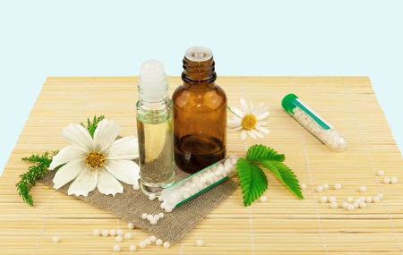 Homeopathic medication with flowers and leaves on the mat Stock Photo