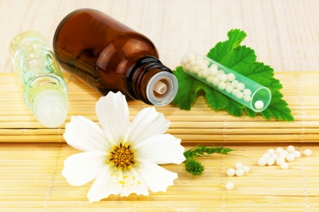 Homeopathic medication with flower and leaf on the mat Stock Photo