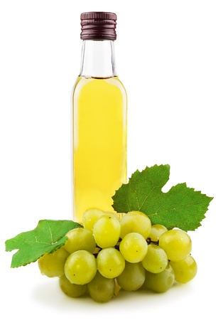 Glass bottle of green wine vinegar with a bunch of grapes isolated on white background Stock Photo