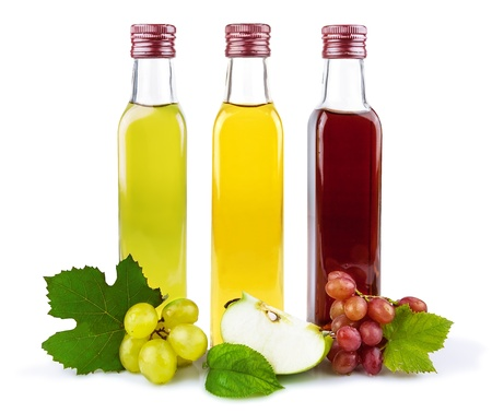 Glass bottles of three kind of vinegar with fruit and leaves isolated on white background
