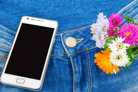 White mobile phone in pocket of blue jeans with flowers photo