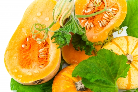 Cut pumpkin with pumpkin seeds and green leaves isolated on white background Stock Photo - 18011072