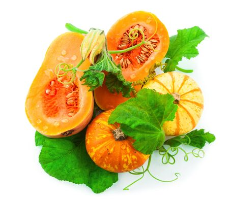 Cut pumpkin with pumpkin seeds and green leaves isolated on white background Stock Photo