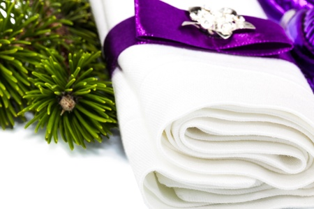 Macro view of white napkin with ribbon and twig Christmas tree isolated on white background Stock Photo