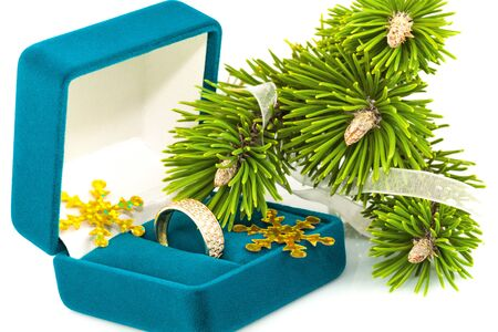 Box with golden ring and twig Christmas tree isolated on white background photo