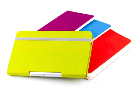 Colourful notebooks with ballpoint pen isolated on white background