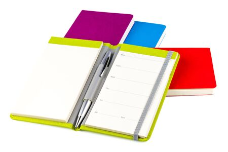 Colourful notebooks with open notebook and ballpoint pen isolated on white background Stock Photo