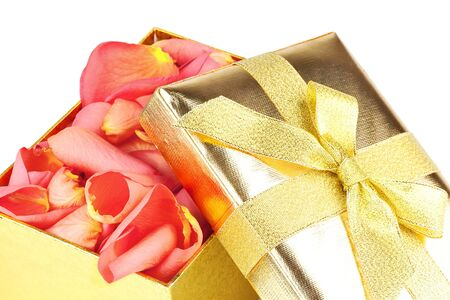Golden box full of roses petals isolated on white background photo