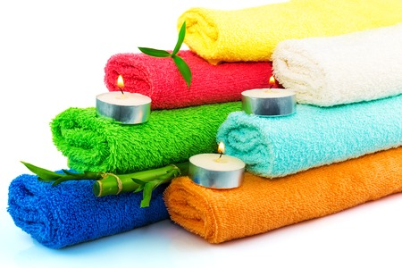 Towels of different colors with candles and bamboo on white Stock Photo