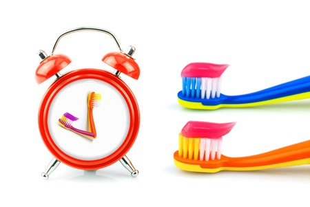 Composition from red clock, toothbrushes with pink toothpaste isolated on white background Stock Photo