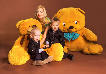 Mother with two sons and two teddy bears on brown background