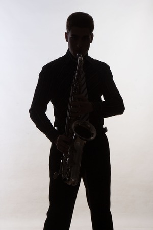 saxophonist: Saxophonist silhouette on grey background Stock Photo