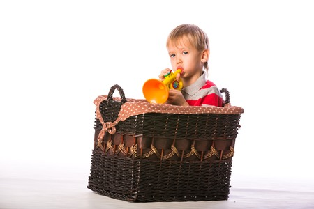 Boy with toy in basket on the floor isolated on white background