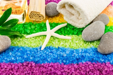 Color sea salt rainbow with shell, stones, aroma oil, bath towel, mat and green leaves