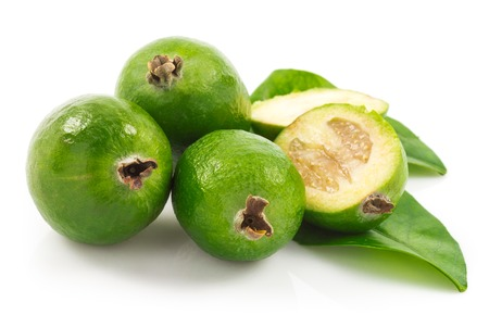 Macro view of feijoa with slices of fruit and green leaves isolated on white background Stock Photo