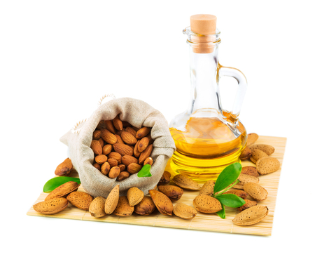 Almonds in the sack, almond oil and green leaves on mat isolated on white background Stock Photo