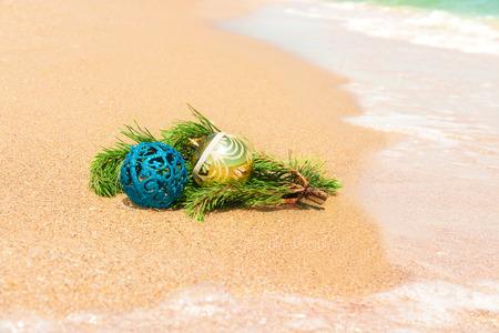 fir twig: Christmas balls with fir twig on sand and sea Stock Photo