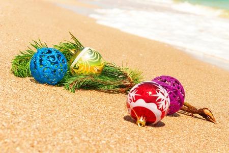 fir twig: Macro view of christmas balls with fir twig on sand and sea Stock Photo